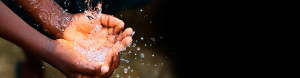 A child's hands cupped together catching falling water