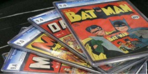 Four collectible comics spread out with Batman comic on top