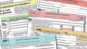 Various tax forms spread out across image