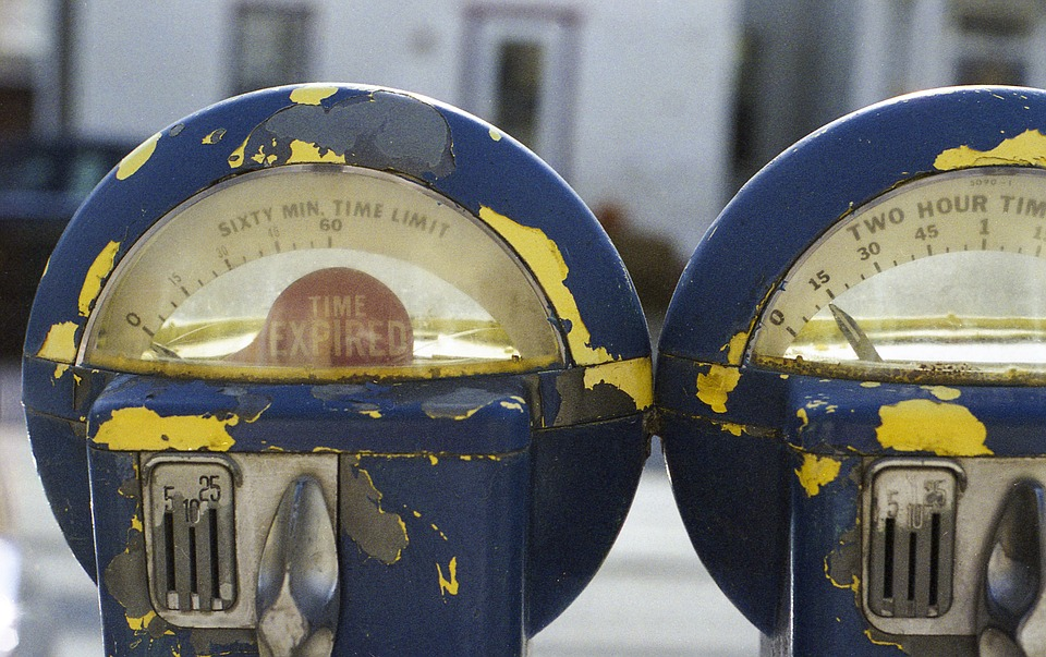 Two parking meters side by side. One expired, the other about to expire.