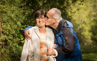Elderly man kissing wife on cheek